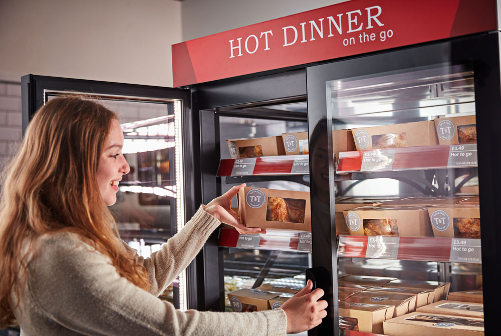 Girl taking rotisserie chicken box out of Flexeserve hot food-to-go unit in supermarket