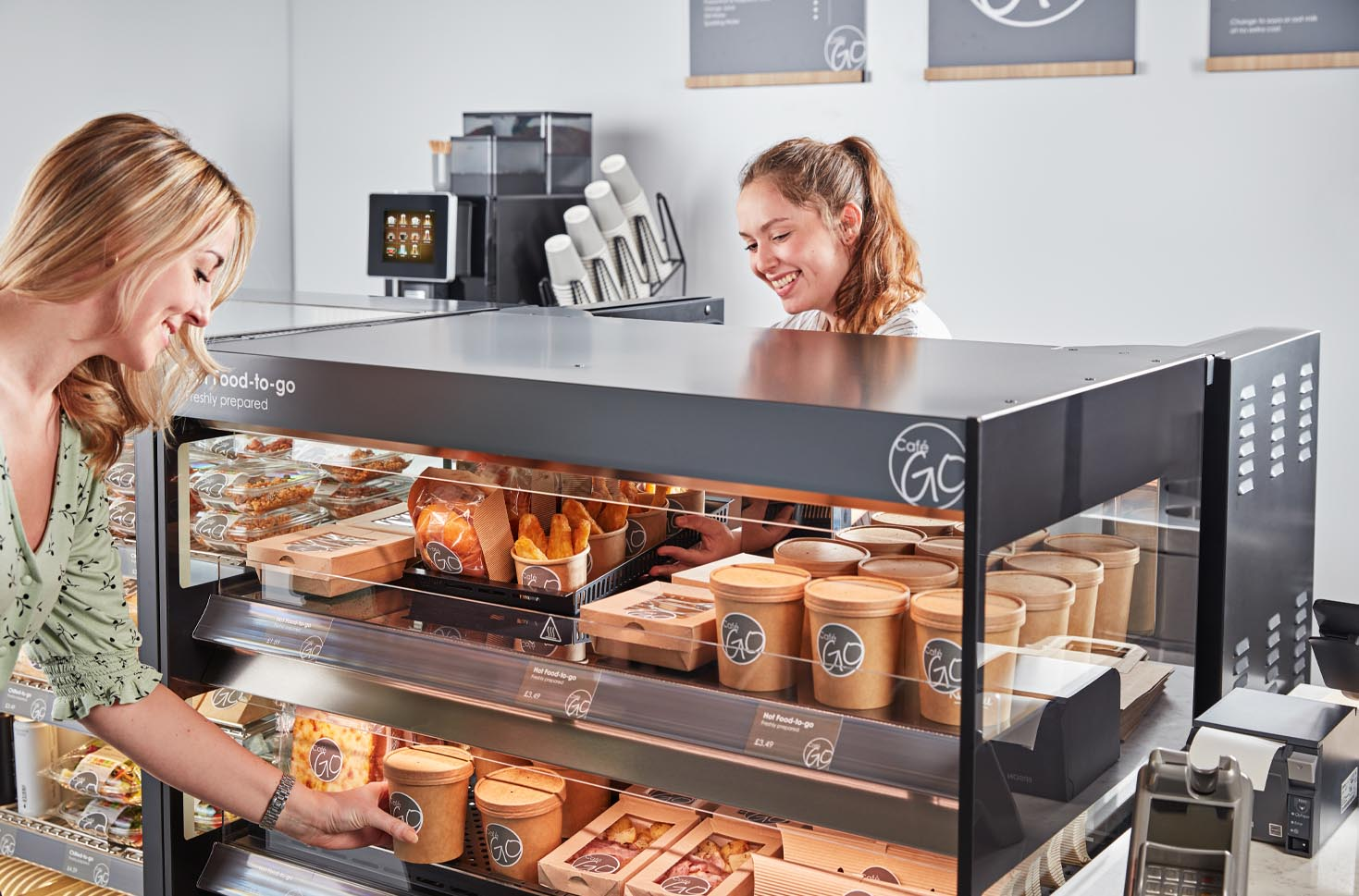A woman restocking Flexeserve Zone Rear Feed hot-holding unit with hot food, from behind the counter, and another woman purchasing hot soup