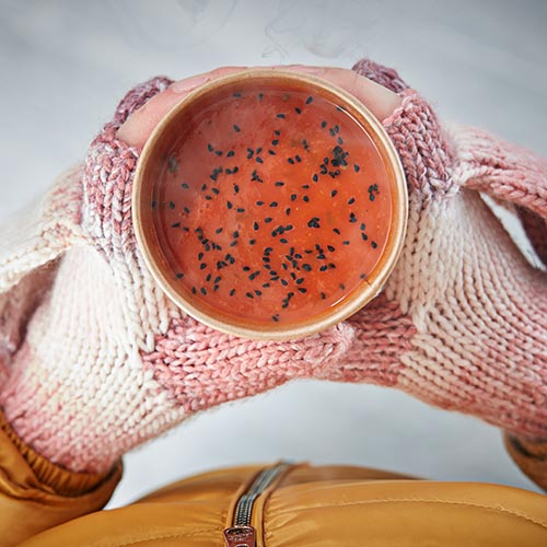 hands wearing pink gloves holding hot soup fresh from a Flexeserve hot-holding unit