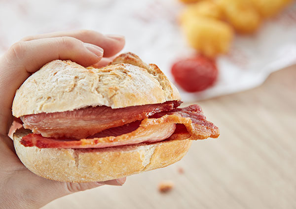 Hand holding bacon sandwich - food-to-go from a Flexeserve heated display